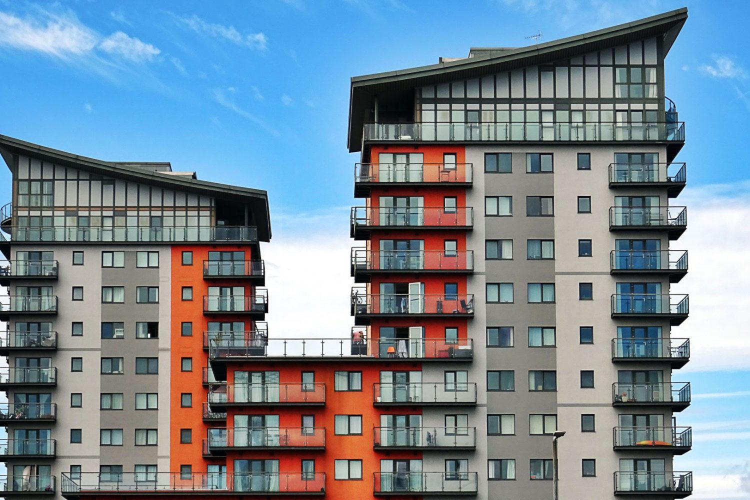 New Build Block of Flats with gray and orange fascias and glass balconies